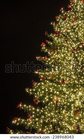 Christmas tree with golden lights and red bows at Frankfurt-at-Main, Germany - New Year and Christmas background and postcard - stock photo