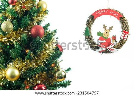 Christmas tree with raindeer decoration isolated on white with copy space for text. Seasonal image of decorated fir tree. - stock photo