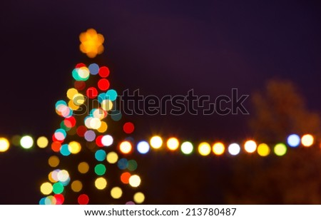 Christmas tree with unfocused bauble in the night - stock photo