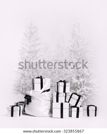 Christmas trees with bag and heap of gift boxes. Studio shot, black and white image - stock photo