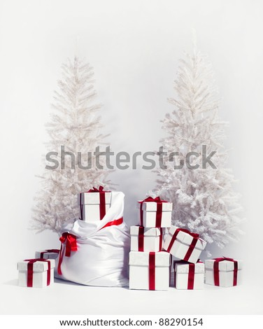 Christmas trees with heap of gift boxes over white background - stock photo