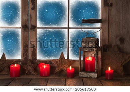 Christmas window decoration with red burning candles and a lantern for a background. - stock photo