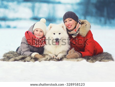 Christmas, winter and people concept - happy smiling family, mother and son walking with white Samoyed dog in winter day - stock photo