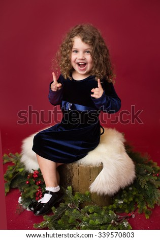 Christmas, Winter Holiday themed setup: child laughing and pointing, ornaments and decorations on red background, sitting on tree stump with branches - stock photo