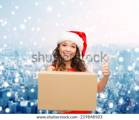 christmas, winter holidays, delivery, gesture and people concept - smiling woman in santa helper hat with parcel box showing thumbs up over snowy city background - stock photo