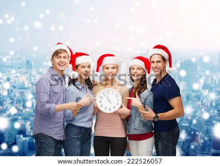 christmas, winter, holidays, time and people concept - group of smiling teenagers in santa helper hats with clock pointing finger over snowy city background - stock photo