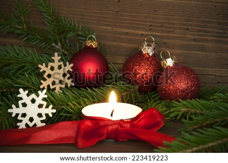 Christmas, Winter or Advent Background with Copy Space in red Colors with a Candle and Winter Decoration on Wood - stock photo