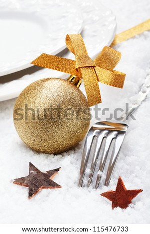 Christmas winter place setting on snow with silver cutlery decorated with a golden bauble and stars - stock photo