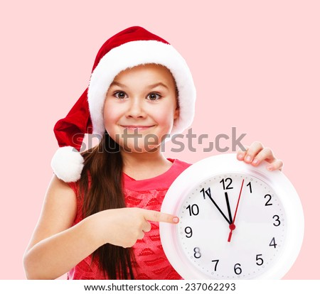 Christmas, winter, time and people concept - girl in santa helper hat with clock - stock photo