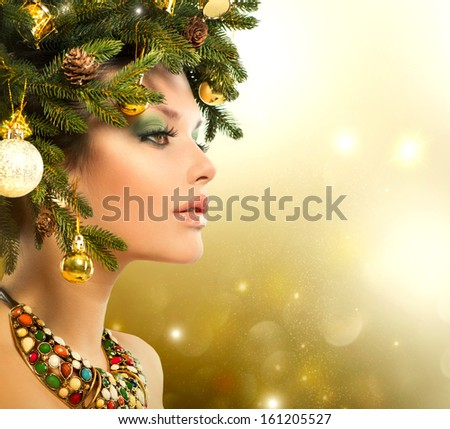 Christmas Winter Woman. Beautiful New Year and Christmas Tree Holiday Hairstyle and Make up. Beauty Fashion Model Girl over Holiday Blinking Background. Creative Hair style decorated with Baubles  - stock photo
