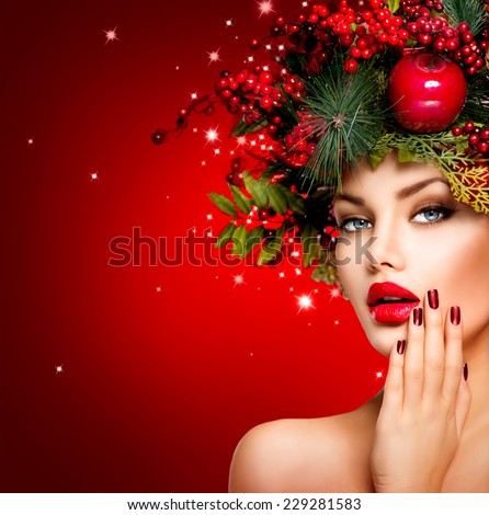 Christmas Winter Woman. Beautiful New Year and Christmas Tree Holiday Hairstyle, Make up, manicure. Beauty Fashion Model Girl over holiday red Background. Creative Hair style decorated with Baubles  - stock photo
