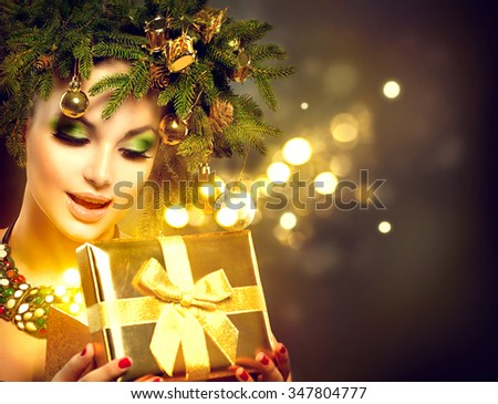 Christmas Winter Woman opening magic Christmas Gift box. Fairy. Beautiful New Year and Christmas Tree Holiday Hairstyle and Make up. Beauty Fashion Model Girl With Present Box. Holiday Magic stars - stock photo
