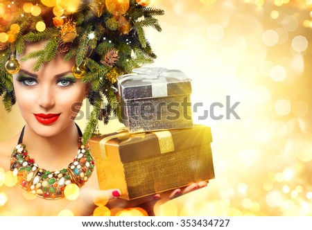 Christmas Winter Woman with Christmas Gifts. Fairy. Beautiful New Year and Christmas Tree Holiday Hairstyle and Make up. Beauty Fashion Model Girl With Present Box over golden glowing background - stock photo