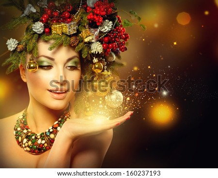 Christmas Winter Woman with Miracle in Her Hand. Fairy. Beautiful New Year and Christmas Tree Holiday Hairstyle and Make up. Magic. Beauty Fashion Model Girl over Holiday Blinking Background.  - stock photo