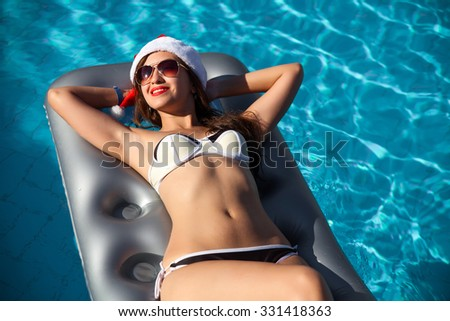 christmas woman beautiful smiling in Santa's hat with a cocktail in the pool in Egypt - stock photo