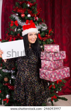 Christmas woman holding stack of presents and showing white blank paper - stock photo