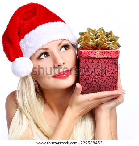 Christmas Woman with Gift Box. Beautiful Blonde Girl in Santa Hat isolated. Portrait - stock photo