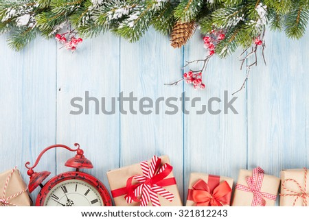 Christmas wooden background with snow fir tree, alarm clock and gift boxes. View with copy space - stock photo
