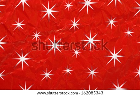 Christmas wrapping paper in a generic white star on red pattern for use as a background. Paper is crumpled and creased as if used. - stock photo