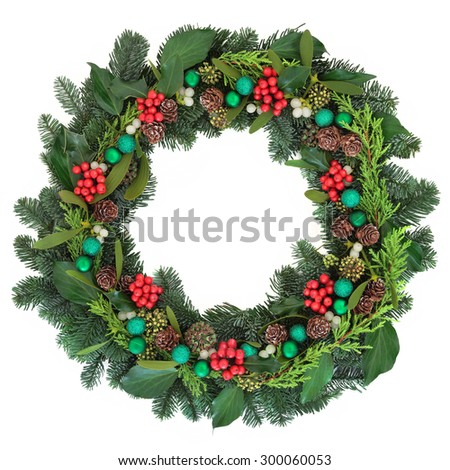 Christmas wreath decoration with green baubles, holly, mistletoe, ivy, pine cones and blue spruce fir over white background. - stock photo