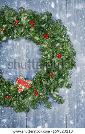 Christmas wreath hanging from rustic door with falling winter snow - stock photo