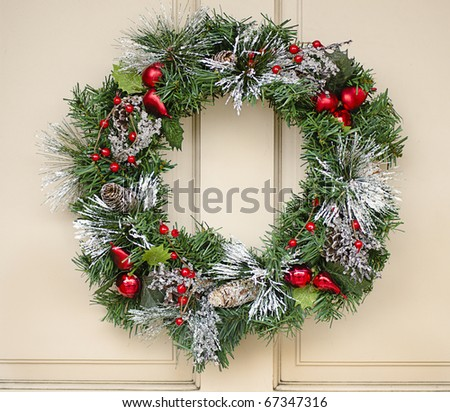 Christmas wreath hanging on painted wooden door - stock photo