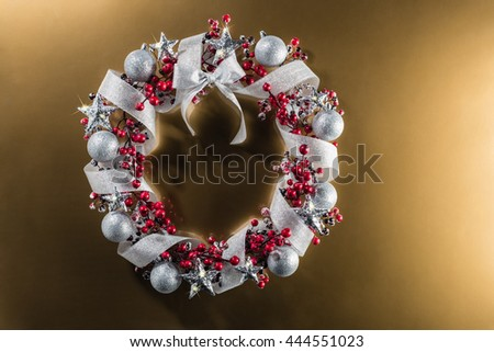 Christmas wreath in red with silver ribbon over plain color background - stock photo