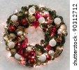 Christmas wreath lit on snowy background - stock photo