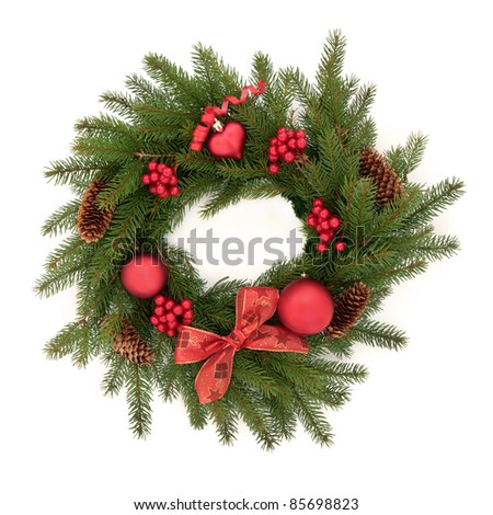 Christmas wreath made of blue spruce fir pine with red bauble decorations, berry clusters, pine cones and bow isolated over white background. - stock photo