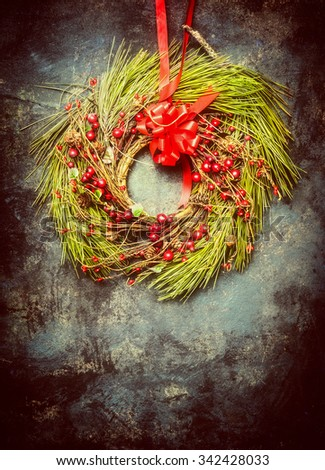 Christmas wreath made ??of fir branches and red winter berries on vintage background. Retro  style - stock photo