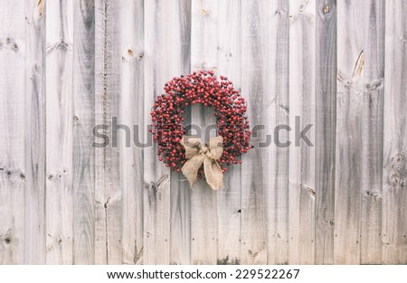 Christmas wreath made of holly berries is tied with a burlap bow and is hanging on old weathered wood. Vintage filters applied.  - stock photo