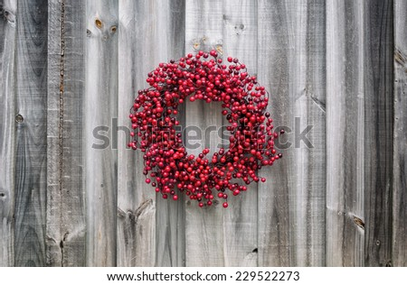 Christmas wreath made of sprigs of holly berries hangs on old weathered wood.  - stock photo