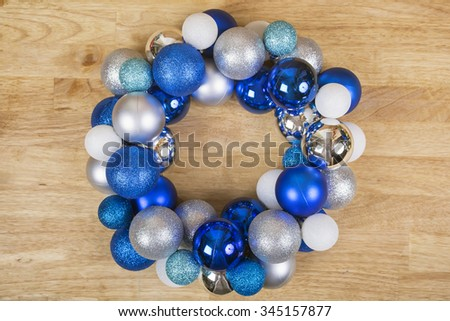 Christmas wreath of blue and white balls on wooden surface. Top view, horizontal. For background or greeting card. - stock photo