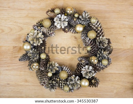 Christmas wreath of cones and gold balls on wooden background. - stock photo