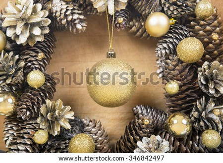 Christmas wreath of cones with gold ball in the center on wooden background close-up.  - stock photo