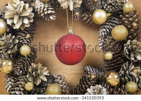 Christmas wreath of cones with red ball in the center on wooden background close-up.  - stock photo