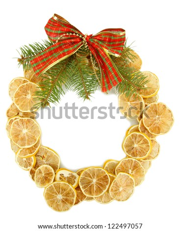 christmas wreath of dried lemons with fir tree and bow isolated on white - stock photo