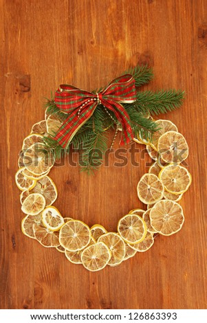 christmas wreath of dried lemons with fir tree and bow, on wooden background - stock photo