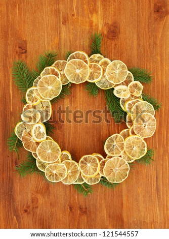 christmas wreath of dried lemons with fir tree, on wooden background - stock photo