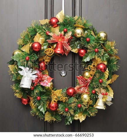 christmas wreath on dark wooden door with peephole in the center - stock photo