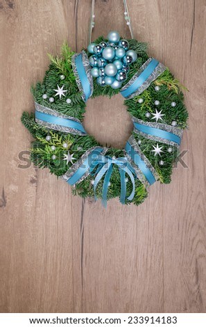 Christmas wreath on wooden door, space for your text - stock photo
