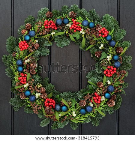 Christmas wreath with blue bauble decorations, holly, mistletoe, pine cones and spruce fir over dark oak wood front door background. - stock photo