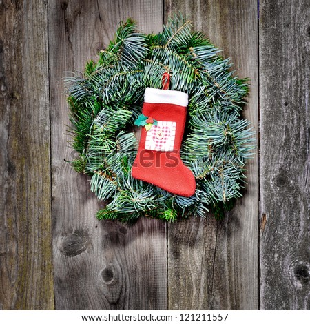 Christmas wreath with christmas sock on the wooden background - stock photo