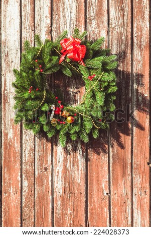 Christmas wreath with decorations on the shabby wooden door. - stock photo