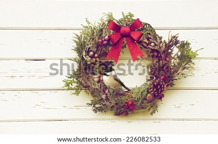 Christmas wreath with natural decorations hanging on a rustic wooden wall with a cute chickadee perched. - stock photo