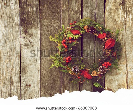 Christmas wreath with natural decorations hanging on a rustic wooden wall with copy space. - stock photo