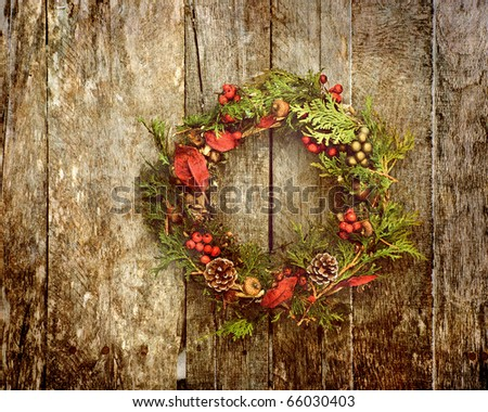 Christmas wreath with natural decorations hanging on a rustic wooden wall with copy space.  Heavily grunge textured. - stock photo