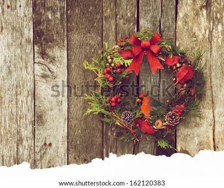 Christmas wreath with natural decorations with a beautiful male  Northern Cardinal peeking out,  hanging on a rustic wooden wall with copy space.  - stock photo