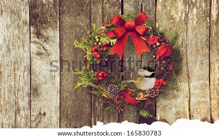Christmas wreath with natural decorations with a cute chickadee perched, hanging on a rustic wooden wall with copy space.  - stock photo