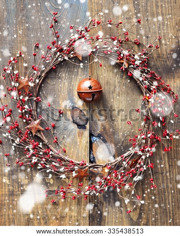 Christmas wreath with red and white berries and rusty metal stars on wooden background. Falling snow effect. Vintage Style. Toned image - stock photo